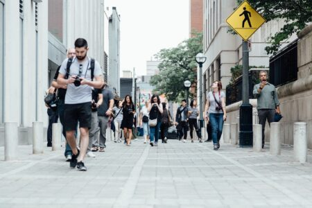 crowd of millennials walking on sidewalk